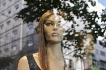 Mannequins behind glass reflecting street buildings — Stock Photo