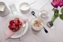 Café y tarta de fresa en la mesa - foto de stock