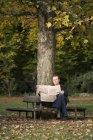 Uomo maturo seduto sulla panchina del parco a leggere un giornale — Foto stock