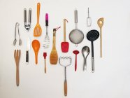 Kitchen utensils hanging on white wall — Stock Photo