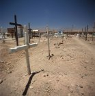 Crosses at cemetery in barren landscape on sunny day — Stock Photo