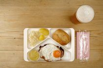 Direkt über dem Tablett mit Ei, Wurst und Brot neben einem Glas Bier — Stockfoto