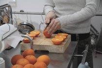 Животик женщина резки апельсины пополам на разделочную доску на кухне — стоковое фото