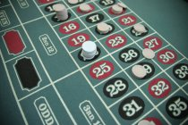 Gambling chips on fields at roulette table — Stock Photo