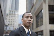 Jeune homme d'affaires debout dans le quartier financier — Photo de stock