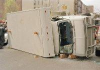 Truck lying on side in city street — Stock Photo