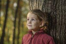 Uma jovem encostada a um tronco de árvore — Fotografia de Stock