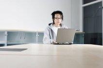 Um homem trabalhando em um laptop em uma mesa de conferência — Fotografia de Stock