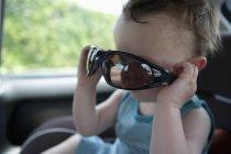 Menino sentado no carro brincando com óculos de sol — Fotografia de Stock