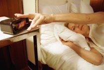 Donna sdraiata a letto con mano sulla sveglia — Foto stock