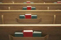 Empty church pews and hymnals — Stock Photo
