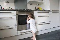 Kleinkind stützte sich auf Ofentür und spähen im Inneren — Stockfoto