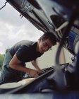 Молодой человек проверяет автомобильный аккумулятор — стоковое фото
