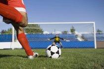 Sección baja de reproductor fútbol tiro libre - foto de stock