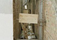 Cardboard sign plate on gate of alleyway — Stock Photo