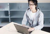 Un uomo asiatico che lavora su un computer portatile — Foto stock