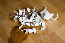 Fracassato tazza di caffè sulla tabella di legno — Foto stock