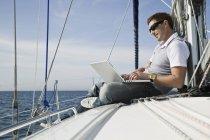 Uomo che utilizza un computer portatile mentre si rilassa su uno yacht — Foto stock