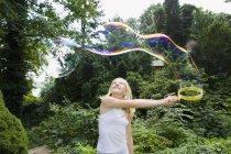 Ragazza facendo bolle con una bacchetta di bolla — Foto stock