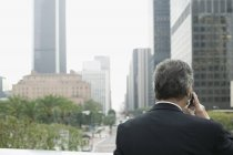 Задній вид бізнесмен, за допомогою мобільного телефону на балконі у фінансовому районі — стокове фото
