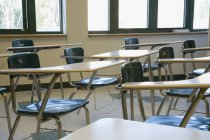Cropped image of empty desks at classroom — Stock Photo