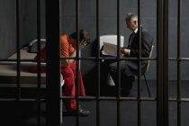 Prisonnier parlant à un avocat dans une cellule de prison — Photo de stock