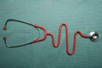 Stethoskop in Form eines normalen Ekg-Graphen auf grünem Hintergrund — Stockfoto