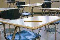 Pencil on desk at empty classroom — Stock Photo