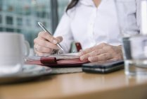Женщина с урожая сидит за столом и использует личный органайзер — стоковое фото