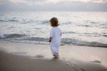 Rückansicht eines Jungen, der in der Abenddämmerung am Strand spaziert — Stockfoto