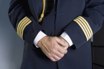 Tronco del pilota in piedi con le mani clasped — Foto stock