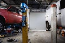 Due auto a mezz'aria in officina meccanica — Foto stock