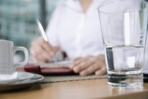 Person writing in note book at table with glass and cup in foreground — Stock Photo