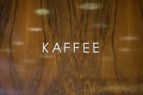 Kaffee lettering on polished wooden wall — Stock Photo