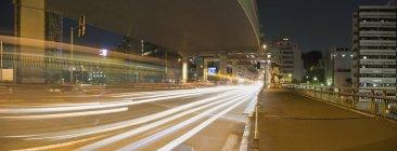 Longue exposition de la circulation passant sur la route la nuit — Photo de stock