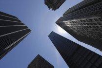 Vista inferiore di grattacieli sopra il cielo pieno di sole libero — Foto stock