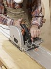 Midsection of man cutting wood with rotary saw — Stock Photo