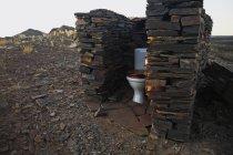 Зовнішні туалет з кам'яною стіною в сільській місцевості field — стокове фото