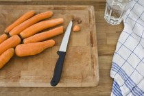 Still life of cutting board with knife and carrots — Stock Photo
