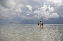 Вид сзади женщины и двух молодых девушек, стоящих в море — стоковое фото
