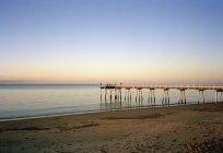 Tranquillo paesaggio marino con molo sopra il tramonto cielo sfumato — Foto stock