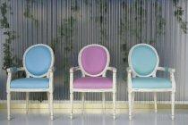 Três cadeiras ornamentadas em fileira sobre a parede de Hera-abraçado — Fotografia de Stock