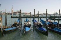 Ряд гондол пришвартован к посту Венецианского канала — стоковое фото