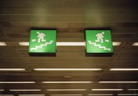 Illuminated emergency exit signs on ceiling — Stock Photo