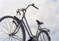 Crop empty old-fashioned bike over cloudscape — Stock Photo