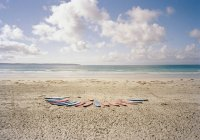 Surfboards in row on idyllic beach — Stock Photo