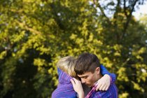 Young couple wrapped in a blanket hugging in park — Stockfoto