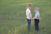 Молодая сестра и брат держатся за руки, на улице — стоковое фото