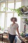 Ritratto di giovane donna in piedi accanto al bancone della cucina contro la finestra di casa — Foto stock