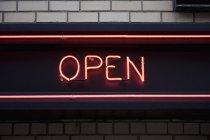 Segno illuminato al neon aperto sulla facciata in mattoni — Foto stock